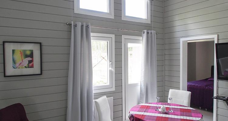 Ikkunaovessa on samanpaksuinen karmi kuin kippi-ikkunassa, joten ne sopivat hyvin yhteen. Kokonaisuuden täydentää kiinteät ikkunat. (Mökki Orimattilassa)